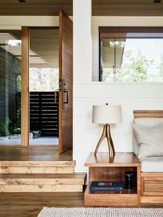 A bright interior with wood front door, wood flooring, and wood sofa frame.
