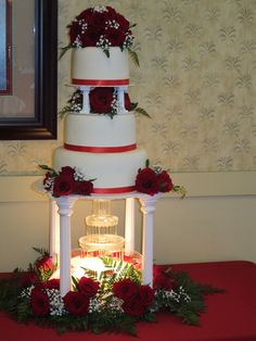 Fountain Wedding Cake - This is a wedding cake we recently made. The bride wanted a fountain and lots of fresh red roses, ferns and babies breath. Carrot cake with cream cheese filling and frosting. Covered in MM fondant.