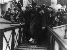 Harold Bride, Titanic's surviving wireless operator, being carried off Carpathia with sprained and frostbitten feet.