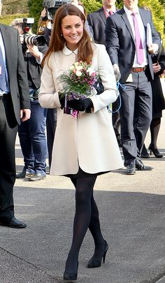 Kate Middleton concealing her baby bump in a winter white jacket.