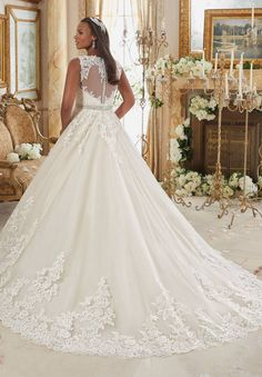 Styled in tulle adorned with embroidered lace appliques, this Mori Lee Julietta…