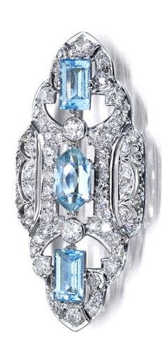 An early 20th century aquamarine and diamond brooch Of scalloped lozenge-shape, set to the centre with a lozenge-shape aquamarine with a baguette-cut aquamarine to either side spaced by a pair of old round brilliant-cut diamonds, all surrounded by a pierced frame set throughout with old round brilliant-cut diamonds and single-cut diamonds, width 45mm