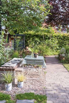 Dekoideen für den Garten im Sommer mit kleinem Teich und Wasserpflanzen, Pflanzen in Kübeln und vielen kleinen Sitzecken