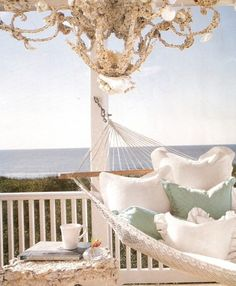 the perfect porch situation: a beachy chandelier, comfy hammock, the best kind of view, and books.  books, books, books.