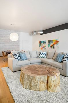 weißes wohnzimmer mit einem großen ecksofa und einem extravaganten tisch aus baumstamm