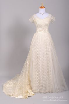 Designed in the 50's this special vintage wedding gown is done in a floral embroidered net over silk with an additional two layers of tulle in the skirt. The bodice offers a scalloped trimmed scooped