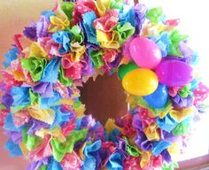 """My Easter Wreath - Styrofoam base with bright happy Easter egg colored fabrics cut with pinking shears into 3 1/2"""" squares which were punched & glued into the base with Mod Podge and a wooden skewer. The egg cluster """"bow"""" was made by threading a single pipe cleaner in & out of the 2 bottom holes in these 5 plastic eggs & then pulling the 2 ends of the pipe cleaner together tightly which bunches & clusters the eggs. Twist & tie pipe cleaner & poke ends into the base between the fabric pieces."""