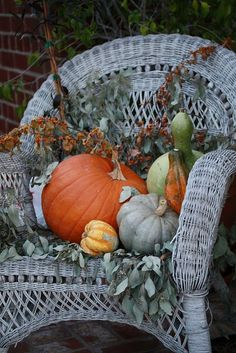 White Wicker Chair On The Porch...with a lovely fall arrangement.