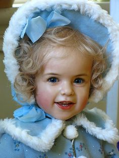 A repin of a doll created by Sissel Bjørstad Skille with blue eyes, blond wavy hair, sky-blue winter coat and hat #doll #girl #Skille