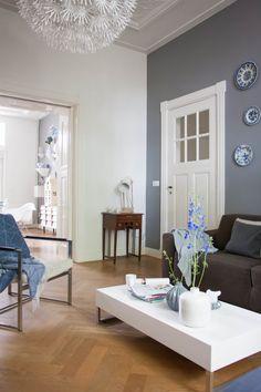 Graue Wand, weiße Tür, blau-weiße Wandteller, Ikea-Lampe