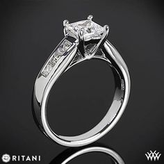 This Diamond Engagement Ring is from the Ritani Classic Collection.  It features a 4 prong head that holds the princess diamond center of your choice and 6 Channel-Set Princess Diamond Melee (0.50ctw