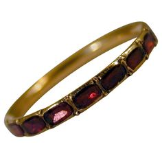 "Antique Garnet and Gold Eternity Ring. Georgian 15K gold and almandine or purplish-red garnet eternity band. Thin bands like this one are hard to find and highly prized. When worn with other rings, for example between two gold bands, they make a wonderful ""look"". Great Britain, circa 1780"