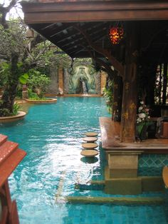 Pool bar in a tropical paradise lined by abstract vegetation and defined by beautifully colored tile and wood.