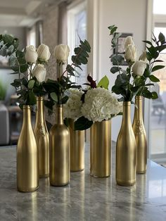 Gold spray painted wine bottles with white roses and eucalyptus. Gold spray painted wine bottles with white roses and eucalyptus. Centerpieces and room decor for a party. Wine Bottle Centerpieces, Wine Bottle Vases, Wedding Wine Bottles, Gold Centerpieces, Diy Bottle, Wine Bottle Crafts, Bottle Art, Wine Bottles Decor, Decorative Wine Bottles
