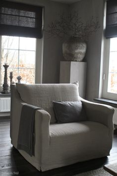linen slip covered chair , grey walls, blind and interesting plinth with pot , great space