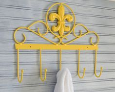 Fleur De Lis multi hook, big enough for five big fluffy towels, hats, scarves, coats, jewelry or anything else youd like to hang on it. It has been hand painted summer squash yellow and lightly distressed. Would look great in the kitchen, entryway, mudroom or nursery.  Approx.