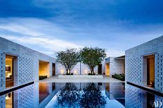 A tranquil retreat outside Phoenix was created by architect Marwan Al-Sayed and designer Jan Showers. The courtyard, centered around a swimming pool disguised as a shallow water feature, is planted with a quartet of Chilean mesquite trees.