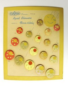 """Display Card, April Showers, 1947  Upright rectangular beige card with yellow boarder around edges; 18 circular yellow, green and orange buttons of various sizes sewn on face, each button a smiling sun with rain drops. printed in upper left corner of card: La Mode [logo], presents """"April Showers""""/ """"designed by Marion Weeber Welsh"""""""