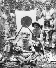 Men of the 3rd New Zealand Division photographed on their return from a fighting patrol with some 'souvenirs' captured from the Japanese, Treasury Islands, Northern Solomons