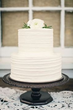 Simple white wedding cake, black cake stand with white flowers. I would put flowers on the side and penguin cake toppers #weddingcakes