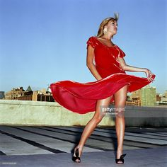 Stock Photo : Young woman standing rooftop, dress blowing in wind