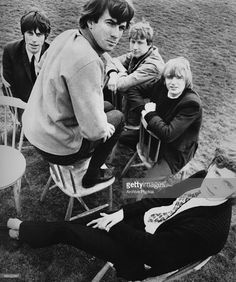 An overhead group portrait of the band The Yardbirds sitting on wooden chairs…