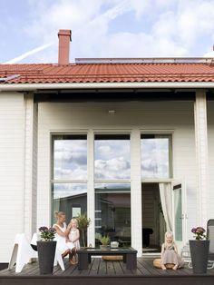 Isot ikkunat päästävät luonnon-valoa sisään. Suuret mustat ruukut ovat Bauhausista Valkoiset tuolit ovat Ikean Vågö-tuoleja, pöytä itse tehty ja musta aurinkotuoli Kodin1:stä. Vesihyasinttityynyt Stockmannilta.