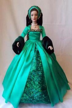 Abito in stile tudor in seta lucida con sottogonna in verde damascato chiaroscuro e maniche in velluto. Corredato dal tipico copricapo alla francese. Costo £245