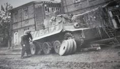 Tiger I undergoing major repairs to its suspension components somewhere in a town. Not unusual for a tank of this size and weight     Tracks and bearings took a toll when road travel was required. Even though there was an internal system for the crew to grease the bearings you have to realize they weren't made to today's standards, but they were the best that could be made at the time.