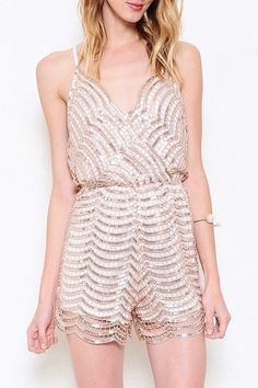 A romper featuring a pattern sequin overlay all throughout. Adjustable shoulder straps. Sleeveless. Surplice front. Elasticized waist. Criss-cross back.