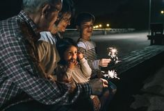 Stock Photo : Grandparents with grandchildren holding sparklers at night