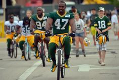 Green Bay Packers defensive end Jarvis Reed rides a kid's bicycle to the opening day of training camp at Nitschke Field. (Benny Sieu-USA TODAY Sports)