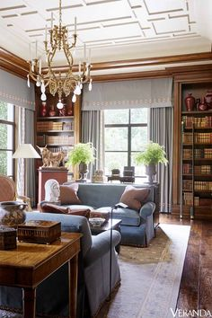 Waxed woods add a layer of patina to the library. Sofas in a Lee Jofa fabric, Cameron Collection; pillows in a Classic Cloth fabric; chandelier, Therien & Co.; task light, Cedric Hartman; floor lamp, Dessin Fournir; curtains in a Holland & Sherry fabric; rug, Scott Group.   - Veranda.com
