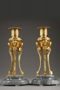 PAIR OF SMALL GILT BRONZE AND TURQUIN MARBLE CANDLESTICKS Beautiful pair of small, gilt bronze tripod candlesticks. They each feature a circular, gray Turquin marble base and three incurvated pilasters that are decorated with acanthus leaves, scrollwork, and veiled female heads, which support the fluted socket. The nozzle is decorated with a frieze of beads and rests on a central, spiraled stem. Circa 1860.