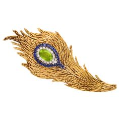 TIFFANY & CO Sapphire Peridot Peacock Feather Brooch US A magnificent Tiffany & Co. brooch consisting of hundreds of hand assembled gold elements, forming a lucious peacock feather, the eye. Peacock Jewelry, Feather Jewelry, Bird Jewelry, Gems Jewelry, Jewelry Design, Jewellery, Jewelry Watches, Peacock Colors, Peacock Feathers
