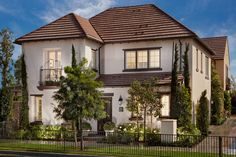 A Juliet balcony and distinctive tile roof define Residence 1, a new home by Irvine Pacific at Marigold. Irvine, CA.