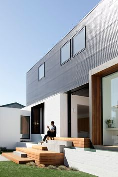 A mix of timber decking and paving steps, that double as seating, lead down to the backyard of this modern house. #OutdoorStairs #ExteriorStairs #Landscaping #Architecture