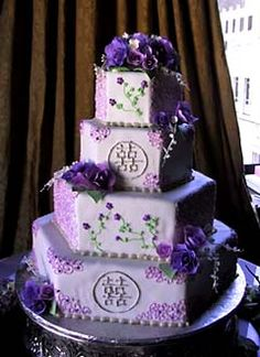 Four tier hexagon shape purple oriental wedding cake, decorated with intricate purple decorations, fresh purple and lilac flowers and Chinese double happiness symbols. From www.butterflycakes.com        ........   #wedding #cake #birthday
