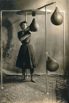 young woman working out with boxing gloves and a punching bag, 1890.