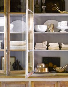 In the dining room, a 19th-century French bookcase is stacked with Astier de Villatte pottery from Kim Fiscus Home, aged European linens, and gleaming antique silver pieces.