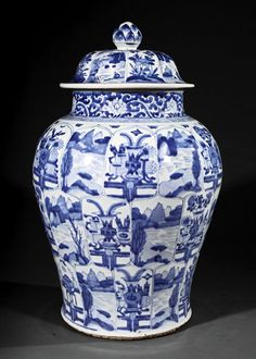 A Large Chinese Blue and White Porcelain Covered Jar, early Kangxi Period (1662-1722), baluster body painted overall with alternating landscape and 'antiques' panels beneath a wide lotus scroll band at the neck, domed cover decorated with alternating floral and landscape panels radiating from a bud knop, height 23 1/2 in.