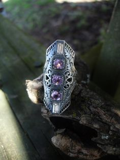 Large oxidized 925 silver ring with three genuine amethyst stones and two cubic zirconia baguettes.  Amethyst is a stone of dreaming and psychic realms as well as a calming and leveling stone said to calm in stressful times and give inner knowledge into dreams and visions.  Kind of art deco kind of steam punk kind of vintage armor but very cool and definitely different. Marked 925 inside of ring  ***Ships out by US Postal Service with insurance in case of loss or damage****