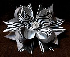 Approximately 4.5 Inch Stacked Hair Bow Zebra Print Grosgrain Ribbon with Silver Accents Rhinestone Starburst Embellishment Covered Metal Alligator Clip with Slip Resist Rubber Pad This chic designer