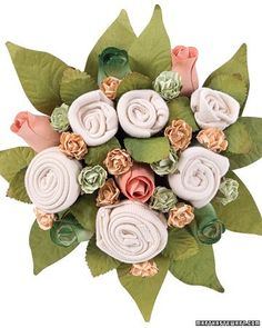"""Shower a new mother with this unique craft of baby essentials wrapped in a pretty arrangement. Use onesies, bibs, hats, socks, or a combination for """"flowers"""" of varying size."""