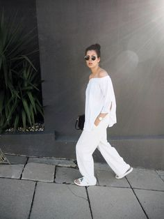 Elisa from www.schwarzersamt.com is wearing an allwhite summer look with MANGO pants, SHEIN offshoulder blouse, CALVIN KLEIN slipper, H&M sunnies, &OTHER STORIES earrings. Location: Cape Town, South Africa