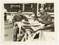 Anonymous | Luftwaffe soldaten op een terras, Anonymous, 1941 - 1942 | Drie Luftwaffe soldaten zitten op een terras. Op tafel staan kopjes en ligt wat lijkt op een tas voor een camera. Van de derde soldaat is alleen de arm te zien. Beide anderen zijn blootshoofd en roken een sigaret. Links achter is nog de ober te zien.