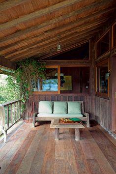 Estar ao ar livre | A varanda termina junto à parede externa da sala da lareira e tem sofá e mesa de madeira bruta desenhados pelo arquiteto (Foto: Marco Antonio/Editora Globo)