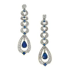A pair of sapphire and diamond pendent earrings   Designed as an openwork pear-shaped pendant set with brilliant-cut diamonds and square-cut sapphire detail, suspending a pear-shaped sapphire swing centre, to a surmount composed of a graduated series of similarly-set scrolls, mounted in 18ct white gold, 5.1cm long, London hallmark