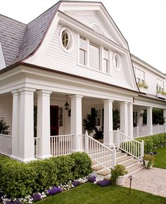 Porch columns. Front porch with columns. Dutch Colonial with fan window, gambrel roof, hanging lantern, hedge, pivot windows. Front Porch light, porch steps, porch potted plants. Porch with white banister #Porch Kathryne Designs, Inc.