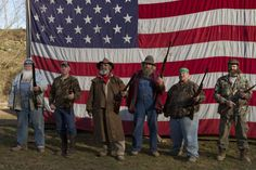 Team AIMS (Appalachian Investigators of Mysterious Sightings) poses in front of an American flag.
